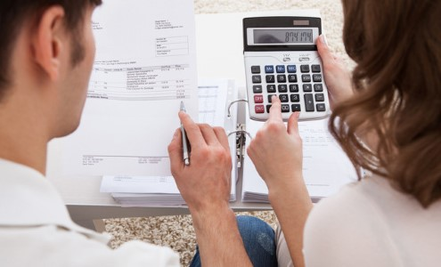 Man and woman working on finances with calculator